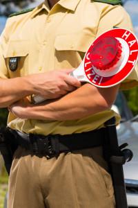 Polizisten zählen die Selkunden, wenn eine rote Ampel überfahren wurde.